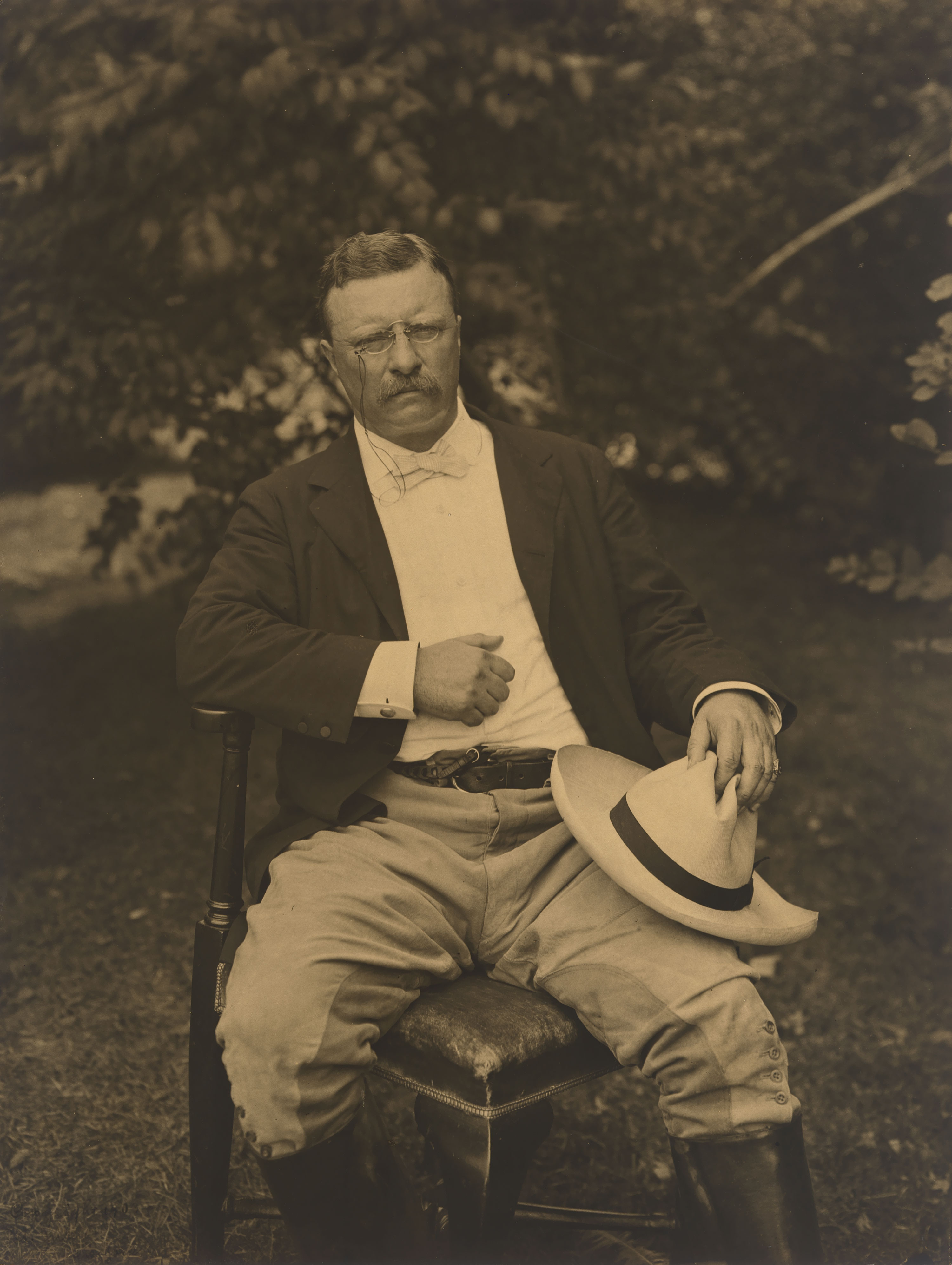 A man (Theodore Roosevelt) is wearing riding clothes, seated in a chair holding a Panama hat on his left leg.