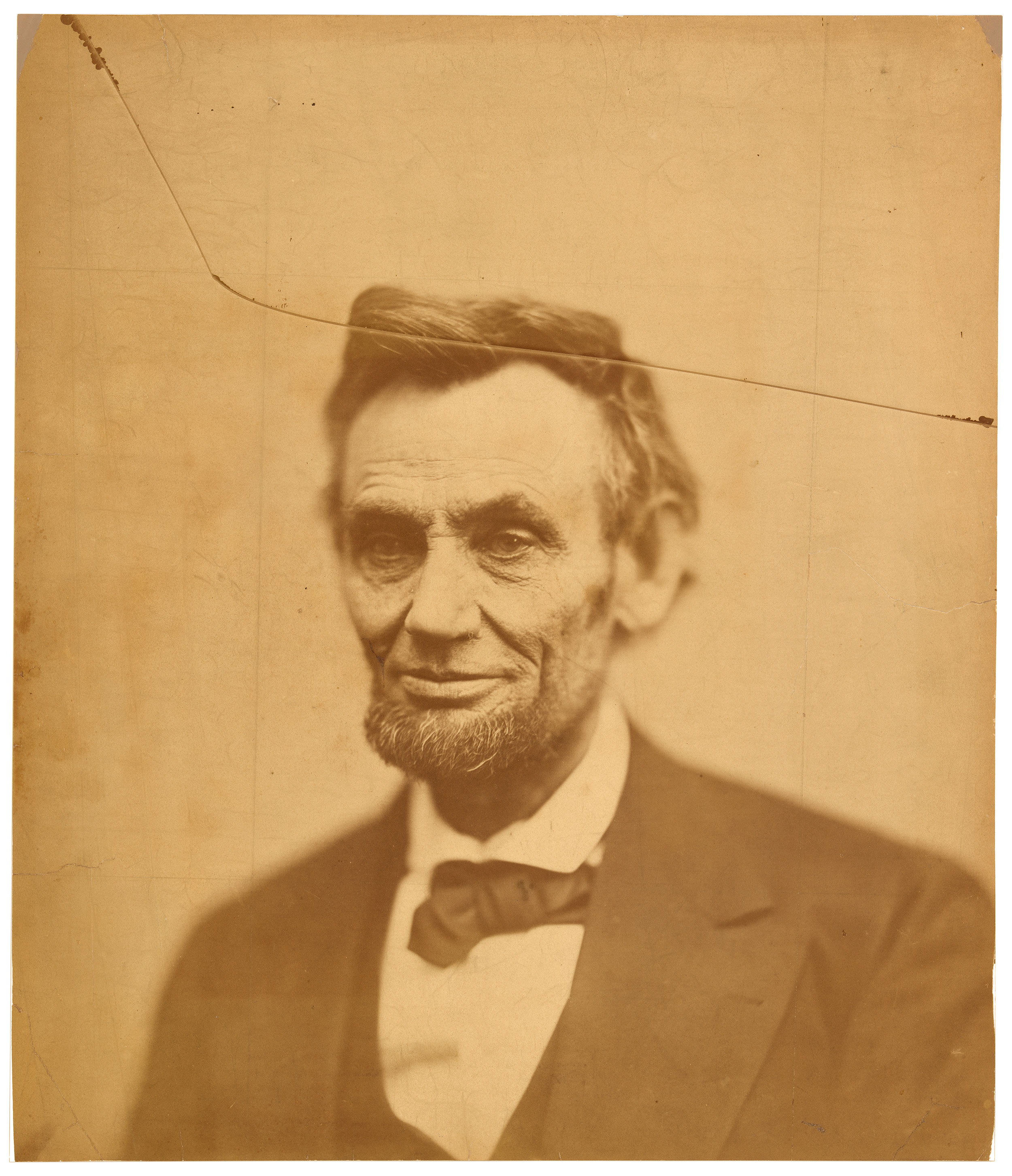 Photograph of Abraham Lincoln in a black suit with a white shirt and black bowtie.  There is a crack across the top of the photo