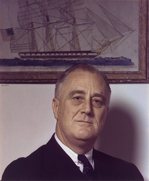 Man (FDR) in a jacket and tie standing before a print of a clipper ship.