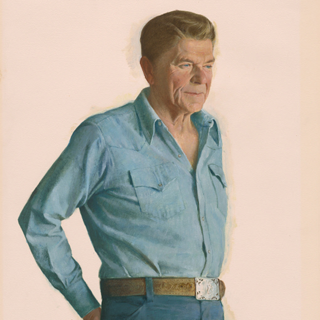 Three-quarter length portrait of a man in blue jeans and a blue workshirt with his hands in his back pockets