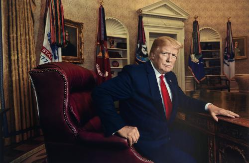 Portrait of a man seated at a desk in the Oval Office